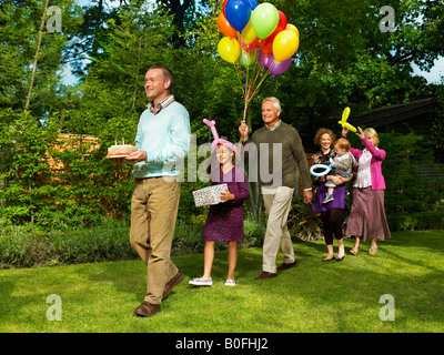 Familie kommen mit Geburtstagstorte - Stockfoto