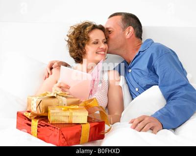 Mann küssen Frau im Bett - Stockfoto
