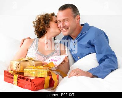 Frau küssen Mann im Bett - Stockfoto