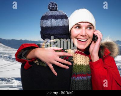 Mann umarmt Frau am Telefon - Stockfoto