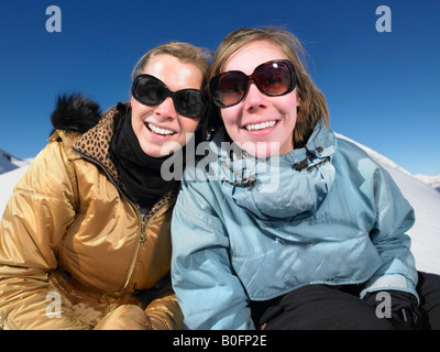 Lächelnde junge Frauen im Schnee - Stockfoto