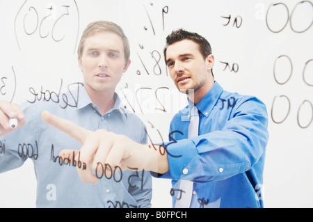 Zwei Männer schreiben auf Glasplatte - Stockfoto