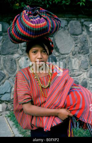 Ein junges Mädchen in Tracht gekleidet geht auf den Markt mit ihren Markt waren auf ihren Kopf in Antigua, Guatemala. - Stockfoto