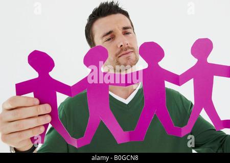 Geschäftsmann hält Papierfiguren - Stockfoto