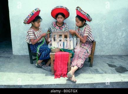 Drei junge Mädchen, gekleidet in traditioneller Kleidung weben Tuch auf dem Platz eines Dorfes im Hochland von Guatemala - Stockfoto