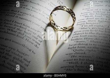 Klingeln Sie in der Falte eines aufgeschlagenen Buches, Schatten bilden ein Herz