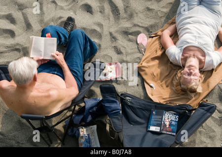 Ehepaar im Ruhestand Mann und Frau am Strand Sonnenbaden und lesen Taschenbücher - Stockfoto