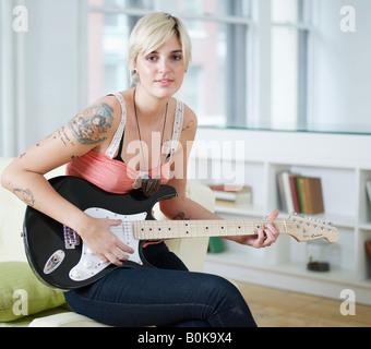 Junge Frau spielt e-Gitarre - Stockfoto