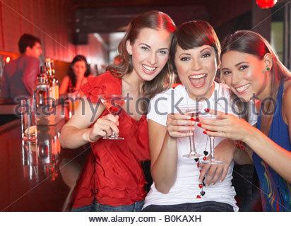 Drei Frauen mit Getränken im Nachtclub Toasten und lächelnd - Stockfoto