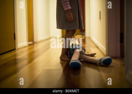 Mädchen im Alter von vier Jahren trägt Spielzeugpuppe in Halle - Stockfoto