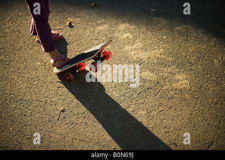 Kleines Mädchen spielt mit einem Skateboard zum ersten Mal rosa Sandalen - Stockfoto