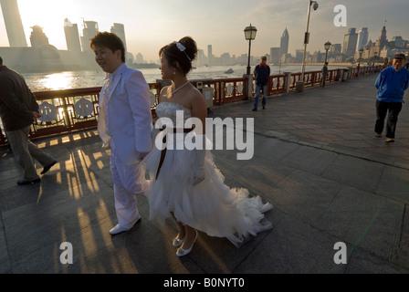 Begrüßen Sie nach der Feier alle Nacht junge Braut und Bräutigam Sonnenaufgang am Bund, Shanghai, China - Stockfoto