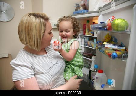 Mutter und Tochter in der Küche das Kleinkind nimmt eine Schokolade süß aus dem Kühlschrank - Stockfoto