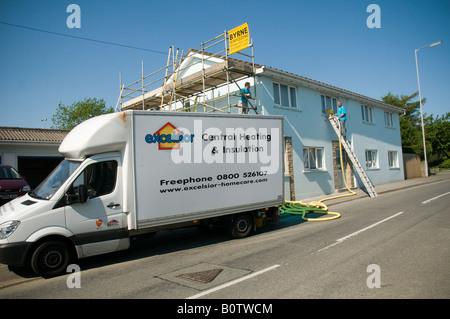 qualifizierte Männer Hohlwand Steinwolle Isolierung anzubringen, in einem Haus zur Verbesserung der Energieeffizienz - Stockfoto