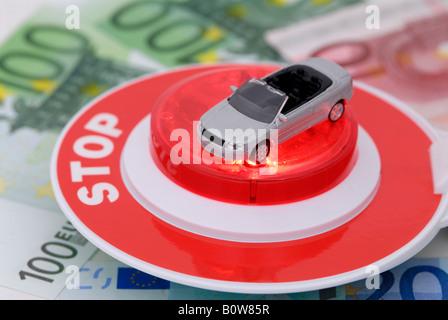 Spielzeug-Auto, Euro-Banknoten, Polizei-Stop-Schild, Symbol für eine Polizeikontrolle - Stockfoto