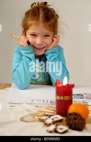 Kleines Mädchen schreiben ihre Weihnachts-Wunschliste für den Weihnachtsmann - Stockfoto