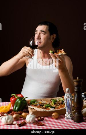 Stereotype italienischen Mann hält eine Glas Weine und Pizza essen - Stockfoto