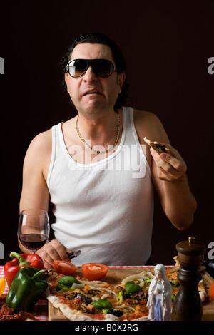 Stereotypen Italiener Pizza essen und hielt ein Messer - Stockfoto