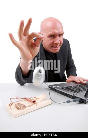 junge Spitze Glatzkopf an seinem Schreibtisch arbeiten hält eine Computer-Maus über die Mausefalle - Stockfoto