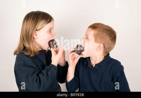 Jungen und Mädchen (8-9) essen Schokolade marshmallows - Stockfoto