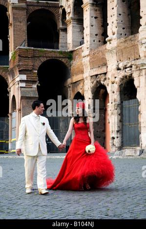 Bräutigam und Braut zu Fuß vor dem Kolosseum, Rom - Stockfoto