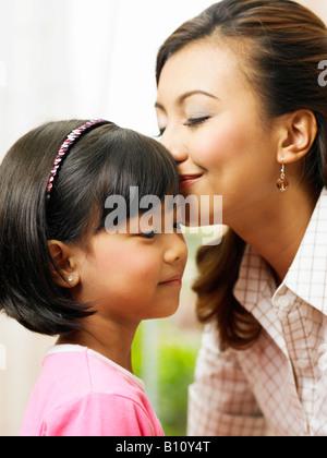 Eine junge asiatische Mutter küsst die Stirn der jungen Tochter - Stockfoto