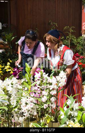 dh FUNCHAL MADEIRA Blumenverkäuferin in traditioneller Tracht, die Blumen an Kunden zu verkaufen - Stockfoto