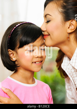 Mutter küssen Tochter auf Stirn - Stockfoto