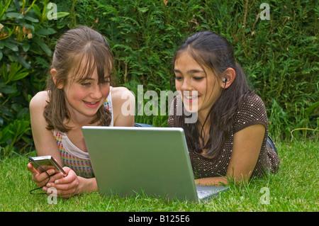 Zwei junge Mädchen (10 Jahre) die besten Freunde in den Garten, Blick auf den tragbaren Rechner mit MP3-Musik-Player - Stockfoto