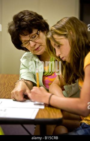 Eine Sonderschullehrerin in einer Mittelschule in Südkalifornien hilft ein Student mit einem mathematischen problem - Stockfoto