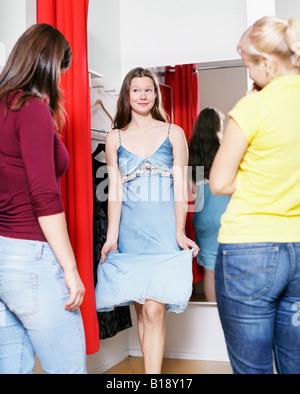 Junge Frau, die versucht, auf ein neues Kleid vor ihren beiden Freundinnen - Stockfoto