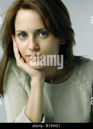 Frau ruhen Kinn in die hand, Blick in die Kamera, Porträt - Stockfoto