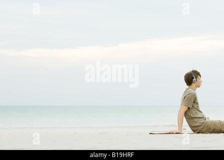 Teen Junge sitzt am Strand hören, Kopfhörer, beschnitten - Stockfoto