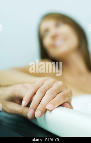 Frau in der Badewanne, des Mannes Hand hält, beschnitten, Ansicht, Fokus auf Händen - Stockfoto