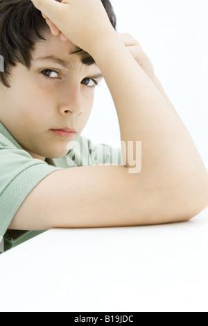 Junge runzelte die Stirn in die Kamera, Kopf haltend, stützte sich auf Ellbogen - Stockfoto