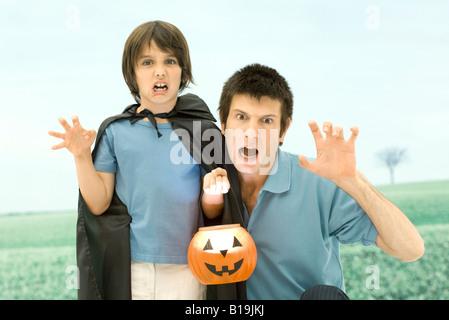 Vater und Sohn halten Jack o' Lantern, furchterregende Gesichter in die Kamera machen - Stockfoto