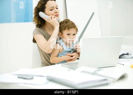 Junge Mutter sitzt am Schreibtisch mit Telefon, während Sohn auf Schoß sitzt, mit Schwert - Stockfoto