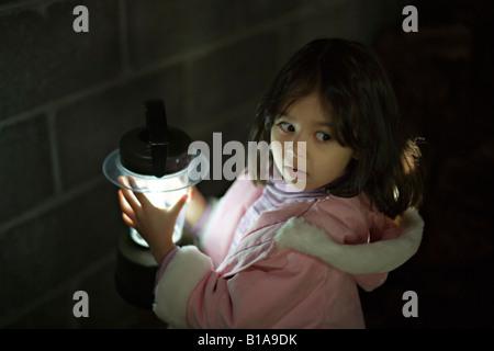 Mädchen im Alter von vier in der Dunkelheit der Garage mit batteriebetriebenen Laterne - Stockfoto