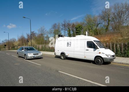 Silber Mercedes Auto beschleunigt vorbei an einem weißen Geschwindigkeit Kamera van im Zentrum der Stadt London - Stockfoto