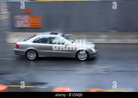 Eine Mercedes-Limousine beschleunigt in einer Straße in Manhattan, New York an einem regnerischen Tag. - Stockfoto
