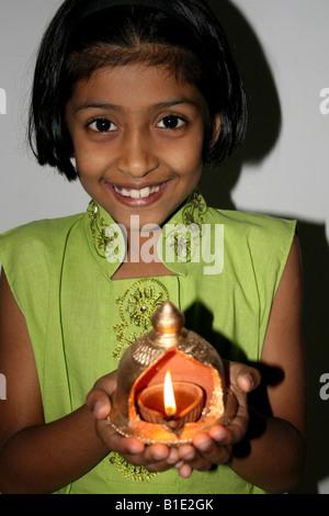 Hindu junge Mädchen halten eine kleine Öllampe Diva für Diwali, Indien - Stockfoto