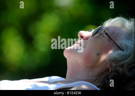 EINE BRITISCHE LADY RENTNER OAP GENIEßT RUHESTAND AN EINEM SONNIGEN TAG SONNENBADEN, UK, ENGLAND. - Stockfoto