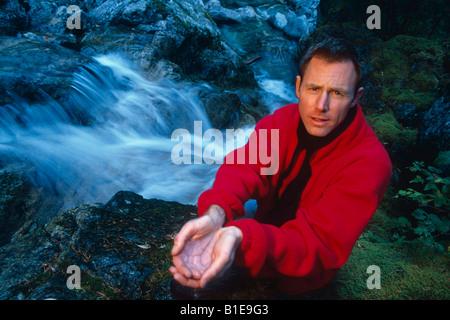 Mann mit Händen schalenförmige halten Wasser aus Bach Washington USA - Stockfoto
