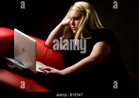 blonde junge Frau, die Arbeit an ihrem weißen Apple Mac iBook-Laptop-Computer sitzt auf einem roten Sofa, e-Mails, - Stockfoto