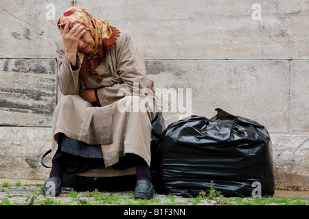 Eine ältere Muslimin weint in die Hand, sitzend vor einer Moschee neben dem großen Basar in Istanbul, Türkei. - Stockfoto