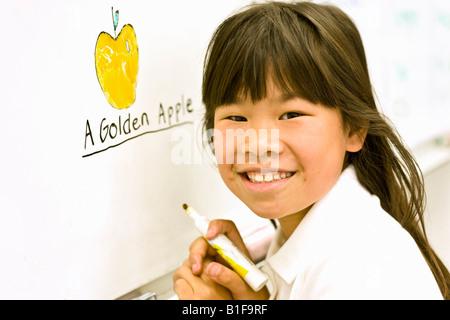 Asiatische Mädchen neben whiteboard - Stockfoto