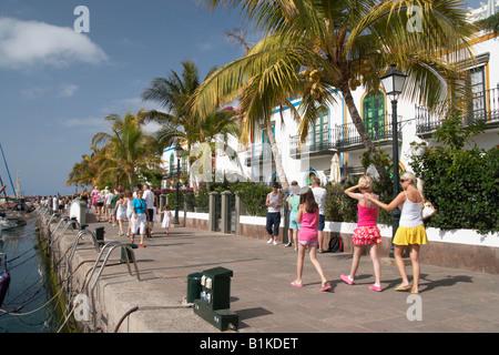 Touristen zu Fuß rund um den Yachthafen in Puerto de Mogan auf Gran Canaria auf den Kanarischen Inseln. - Stockfoto