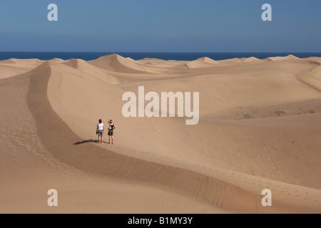 Zwei junge Frauen, die zu Fuß in die Dünen in Maspalomas auf Gran Canaria auf den Kanarischen Inseln. - Stockfoto