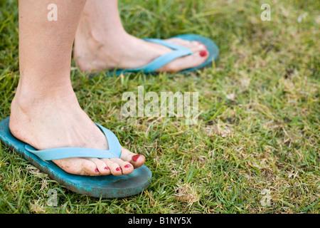 Frau die Füße und Zehen im Schmutz von Gartenarbeiten in blauen Sandalen auf Rasen mit rot lackierten Zehennägeln bedeckt