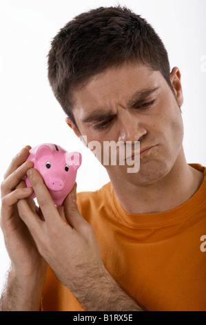 Unbekannter Mann hält ein Sparschwein an seinem Ohr - Stockfoto